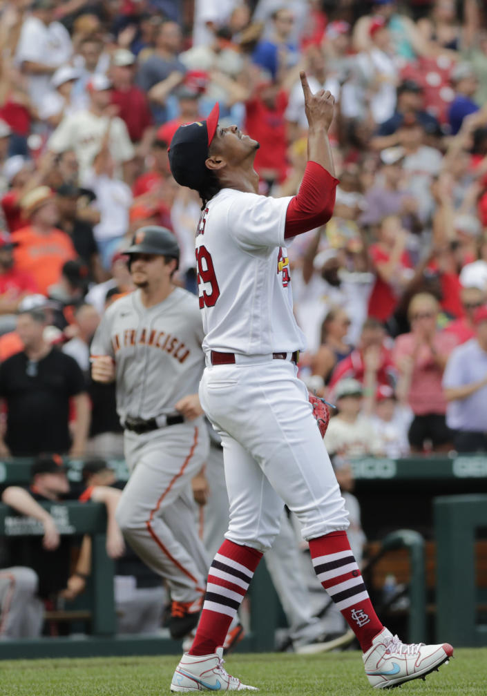 St. Louis Cardinals closing pitcher Alex Reyes, foreground, points skyward after finishing off the San Francisco Giants as Giants' Alex Dickerson, back left, rounds third base in the ninth inning of a baseball game, Sunday, July 18, 2021, in St. Louis. (AP Photo/Tom Gannam)
