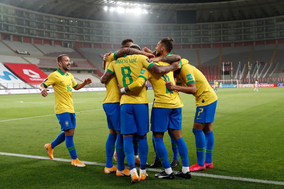 Brazil's players celebrate after teammate Neymar (covered) scored against Peru during their 2022 FIFA World Cup South American qualifier football match at the National Stadium in Lima, on October 13, 2020, amid the COVID-19 novel coronavirus pandemic. (Photo by Paolo Aguilar / POOL / AFP) (Photo by PAOLO AGUILAR/POOL/AFP via Getty Images)