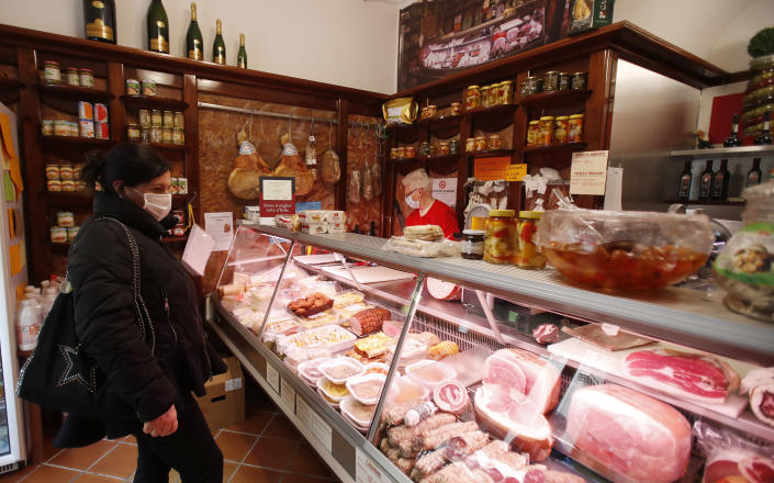 In this photo taken on Thursday, March 12, 2020, a client wearing a mask stands in a deli meat and cold cuts shop in Codogno, Italy. The northern Italian town that recorded Italy's first coronavirus infection has offered a virtuous example to fellow Italians, now facing an unprecedented nationwide lockdown, that by staying home, trends can reverse. Infections of the new virus have not stopped in Codogno, which still has registered the most of any of the 10 Lombardy towns Italy's original red zone, but they have slowed. For most people, the new coronavirus causes only mild or moderate symptoms. For some it can cause more severe illness. (AP Photo/Antonio Calanni)