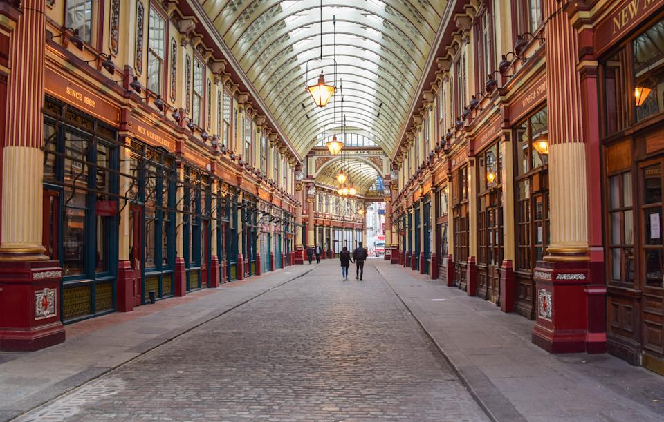 <p>A couple walks past closed shops in Leadenhall Market, London. The coronavirus lockdown restrictions remain in place across the UK. (Photo by Vuk Valcic / SOPA Images/Sipa USA)</p>