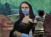 An artist makes a mural of the Monalisa wearing a face mask to spread awareness for the prevention of the coronavirus in Mumbai, India, Wednesday, March 24, 2021. (AP Photo/Rajanish Kakade)