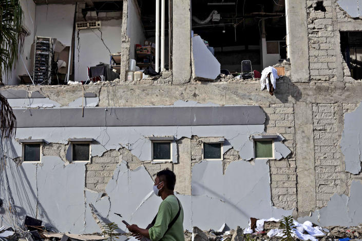A man walks past a building damaged in Friday's earthquake in Mamuju, West Sulawesi, Indonesia, Monday, Jan. 18, 2021. Aid was reaching the thousands of people left homeless and struggling after an earthquake that killed a number of people in the province where rescuers intensified their work Monday to find those buried in the rubble. (AP Photo/Yusuf Wahil)