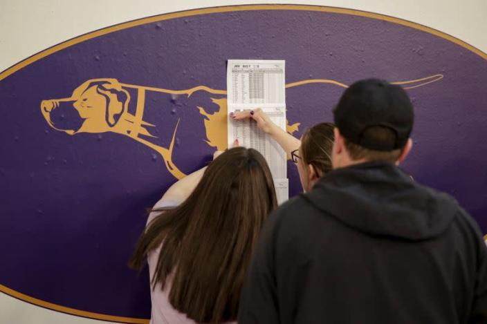 Participants check a lineup list during the Masters Agility Championship during the Westminster Kennel Club Dog Show in New York