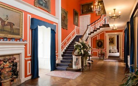 The entrance hall, painted orange in homage to the décor of Woburn Abbey - Credit: christopher jones