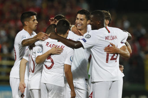 Portugal's Cristiano Ronaldo, center, celebrates with teammates after scoring his side's second goal during the Euro 2020 group B qualifying soccer match between Lithuania and Portugal at LFF stadium in Vilnius, Lithuania, Tuesday, Sept. 10, 2019. (AP Photo/Mindaugas Kulbis)