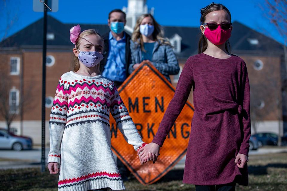 Brienne Babione (left), 9, stands with her sister Blair Babione, 11, as their parents John and Leslie Babione stand in the background, Tuesday, March 2, 2021, a day after the girls visited Carmel City Hall hoping to convince the city to abandon the gendered signage it uses.