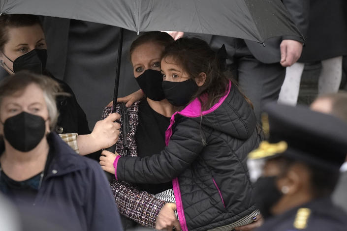 """Shannon Terranova, center left, wife of the late U.S. Capitol Police officer William """"Billy"""" Evans, carries her daughter Abigail Evans, 7, while departing St. Stanislaus Kostka Church with Evan's mother Janice Evans, left, following a funeral Mass for her husband, in Adams, Mass., Thursday, April 15, 2021. Evans, a member of the U.S. Capitol Police, was killed on Friday, April 2, when a driver slammed his car into a checkpoint he was guarding at the Capitol. (AP Photo/Steven Senne)"""