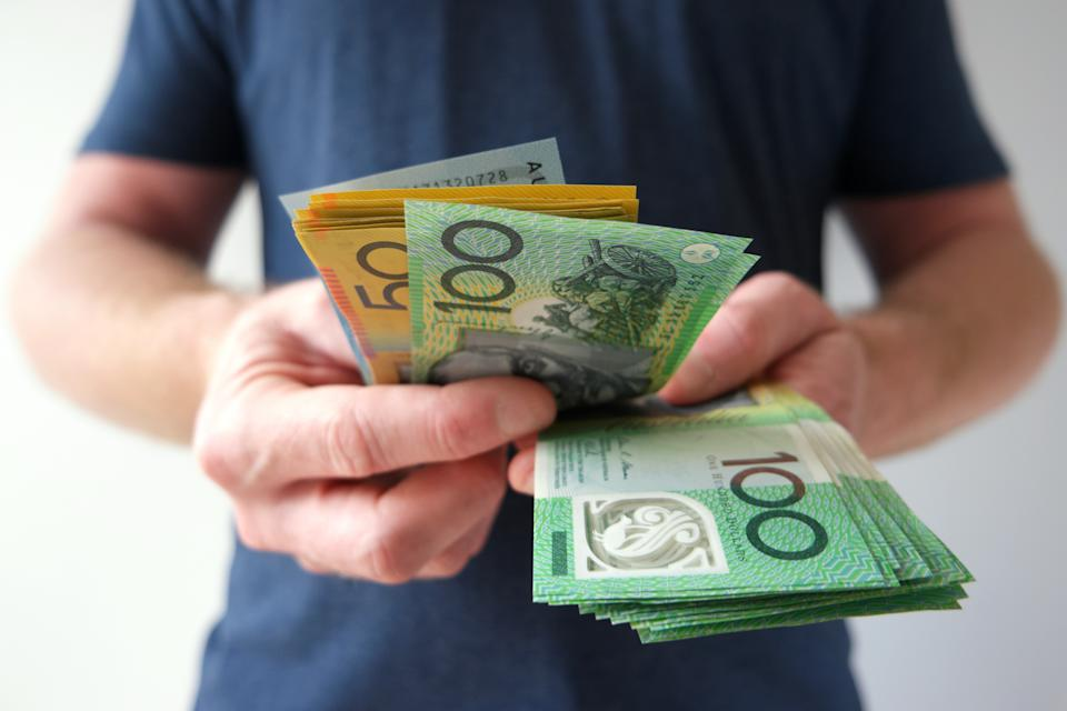 A man counting Australian dollar bills. A picture that describes buying, paying, handing out money, or showing money.