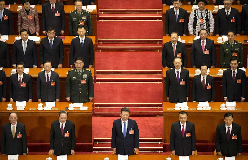 From front left, Wang Qishan, Yu Zhengsheng, Chinese President Xi Jinping, Premier Li Keqiang, and Liu Yunshan stand during the start of the opening session of China's annual National People's Congress in Beijing's Great Hall of the People, Sunday, March 5, 2017. China's top leadership as well as thousands of delegates from around the country are gathered at the Chinese capital for the annual legislature meetings. (AP Photo/Mark Schiefelbein)
