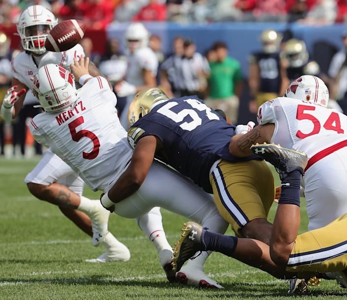 CHICAGO, ILLINOIS - SEPTEMBER 25: Graham Mertz #5 of the Wisconsin Badgers tries to get off a pass as he's hit by Blake Fisher #54 of the Notre Dame Fighting Irish at Soldier Field on September 25, 2021 in Chicago, Illinois. (Photo by Jonathan Daniel/Getty Images)
