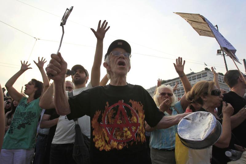 An elderly protester shouts slogans in front of the Greek Parliament during a peaceful rally for a ninth consecutive day, attended by thousands called through a social networking site in Athens, on Monday, June 2, 2011. Talks over new austerity measures required to keep Greece from defaulting on its debts are close to a conclusion, a European official said Thursday. A report from the negotiations will determine whether Greece gets the next installment of its existing rescue loan as well as a potential second bailout to cover its finances through 2013. (AP Photo/Thanassis Stavrakis)