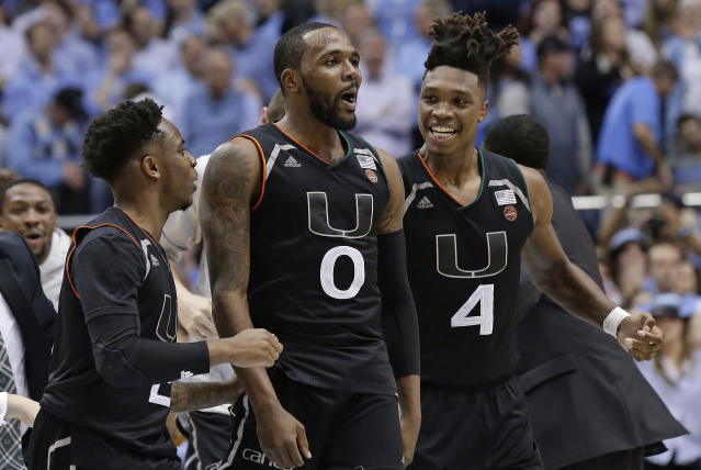 Miami's Ja'Quan Newton (0) celebrates with Lonnie Walker IV (4) and Chris Lykes following Newton's game-winning shot against North Carolina as time expired in an NCAA college basketball game in Chapel Hill, N.C., Tuesday, Feb. 27, 2018. Miami won 91-88. (AP Photo/Gerry Broome)