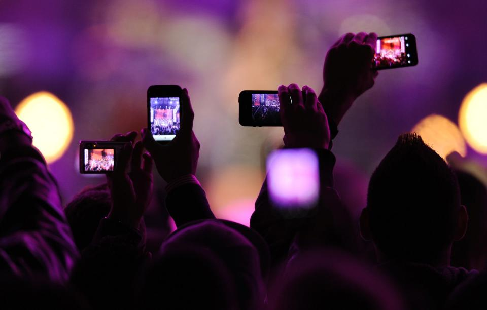"""Fans take photos with their mobile phones during the VH1 """"Divas Salute The Troops"""" show at the Marine Corps Air Station Miramar in San Diego, in this December 3, 2010, file photo. Snapchat, the mobile photo-sharing service beloved by teenagers and twenty-somethings, has raised another $50 million, according to a Securities and Exchange Commission filing made December 11, 2013. The funding brings the total raised by the two-year-old company to more than $123 million. REUTERS/K.C. Alfred/Files (UNITED STATES - Tags: ENTERTAINMENT SCIENCE TECHNOLOGY)"""