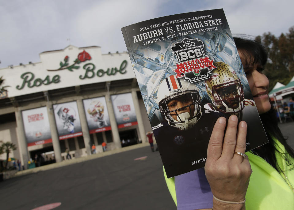 FILE - In this Jan. 6, 2014, file photo, a vendor sells a program outside the Rose Bowl before the BCS National Championship NCAA college football game between Auburn and Florida State in Pasadena, Calif. The Rose Bowl was denied a special exemption from the state of California to allow a few hundred fans to attend the College Football Playoff semifinal on Jan. 1, putting the game staying in Pasadena in serious doubt. A person involved with organizing the game told The Associated Press the Tournament of Roses' request was denied earlier this week. (AP Photo/Chris Carlson, File)