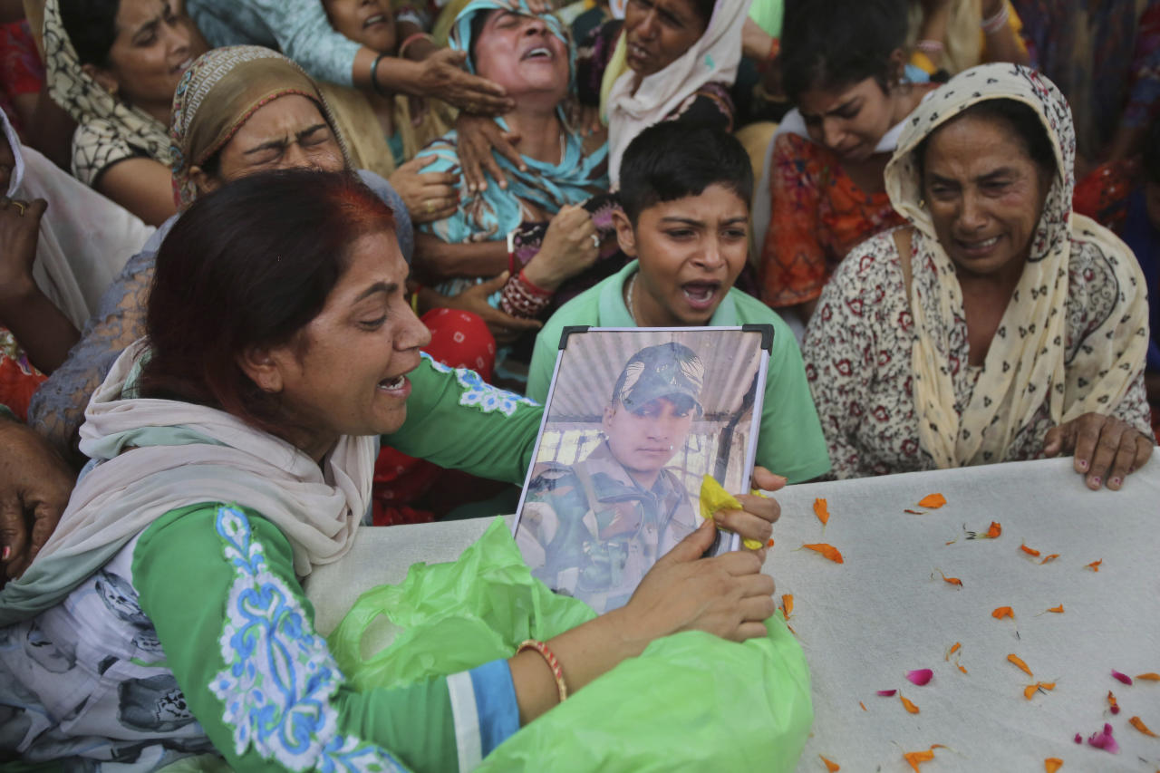 Family members of Indian army soldier Krishan Lal grieve, who was killed in firing from the Pakistan side of the border, at village Ghagriyal in Akhnoor, about 62km (51 miles) from Jammu, India, Wednesday, July.31,2019. India and Pakistan are exchanging heavy artillery fire at the Tangdhar sector near the Line of Control in north Kashmir after Pakistan violated the ceasefire agreement this afternoon.(AP Photo/Channi Anand)