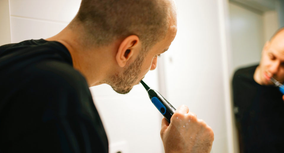 man brushing his teeth with an electric toothbrush in the mirror