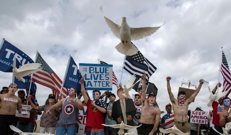 President Donald Trump supporters release doves during a march, in Huntington Beach, Calif. - Credit: Mindy Schauer/Orange County REgister/AP