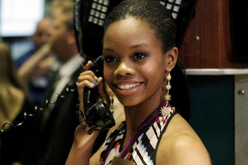 Olympic champion gymnast Gabby Douglas pretends to talk on the phone while posing for photos on the floor of the New York Stock Exchange, Tuesday, Aug. 14, 2012, in New York. (AP Photo/Alex Katz)