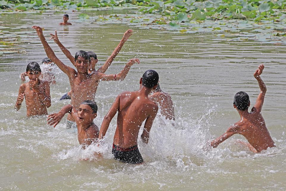 Indian boys take a dip in a pond to get respite from scorching heat on a hot summer day, at Mundia Village of Tonk District in Rajasthan on Monday, June 10,2019.Temperatures in an Indian desert state hit 50 degrees Celsius (122 Fahrenheit) third times in the month of june as a deadly heatwave maintained its grip on the country. (Photo By Vishal Bhatnagar/ NurPhoto via Getty Images) (Photo by Vishal Bhatnagar/NurPhoto via Getty Images)