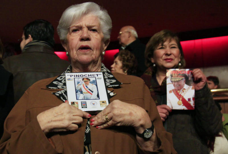 Supporters hold pictures of Gen. Augusto Pinochet during the screening of a documentary in a downtown theater in Santiago, Chile, Sunday June 10, 2012. The film casts Pinochet as a national hero who saved Chile from communism and who died victimized by leftists who accused him of embezzlement and human rights crimes.(AP Photo/Victor Ruiz Caballero)