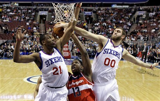 Washington Wizards' Kevin Seraphin (13) battles for a rebound against Philadelphia 76ers' Thaddeus Young (21) and Spencer Hawes (00) in the first half of an NBA basketball game, Friday, Jan. 13, 2012, in Philadelphia. (AP Photo/Matt Slocum)