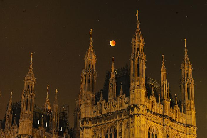 Asuper blood moon rises over the spires of the House of Parliament on September 28, 2015, in London, United Kingdom. (Photo: Joseph Okpako via Getty Images)