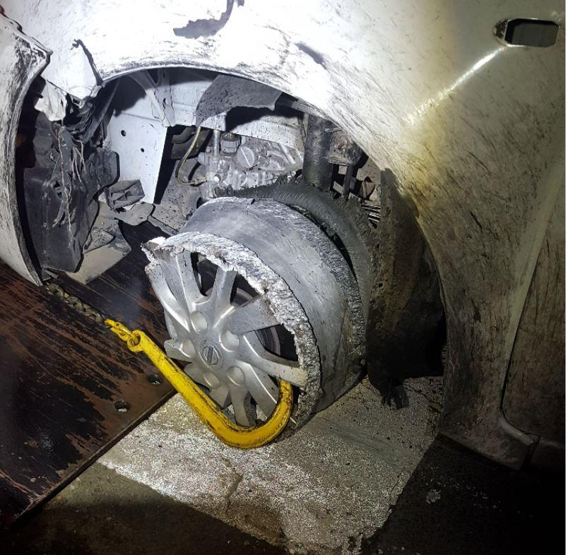 A Nissan Pulsar is pictured with a punctured tyre.