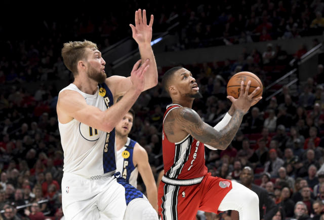 Portland Trail Blazers guard Damian Lillard, right, drives to the basket on Indiana Pacers forward Domantas Sabonis, left, during the second half of an NBA basketball game in Portland, Ore., Sunday, Jan. 26, 2020. Lillard scored 50 points as the Blazers won 139-129. (AP Photo/Steve Dykes)