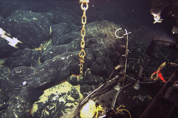 A chain still attached to an ocean-bottom hydrophone (OBH) comes directly out of the seafloor at Axial Seamount where a lava flow erupted in 2011 has buried the instrument to a depth of about 1.5 meters (5 feet). The front of the Jason remotely