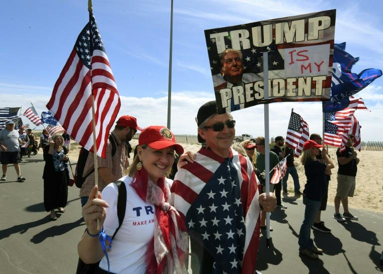 "Supporters of US President Trump march during the ""Make America Great Again"" rally in Huntington Beach, California on March 25, 2017"