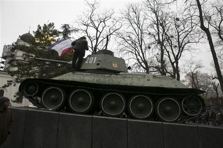 An ethnic Russian Ukrainian man holds the Crimea flag on top of an old Soviet tank during rallies near the Crimean parliament building in Simferopol