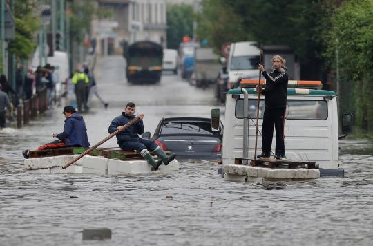 <p>Residents who refused to be evacuated sit on makeshift boats during evacuation operations of the Villeneuve-Trillage flooded suburb in Villeneuve Saint-Georges, outside Paris, France, June 3, 2016 after days of almost non-stop rain caused flooding in the country. (REUTERS/Christian Hartmann) </p>