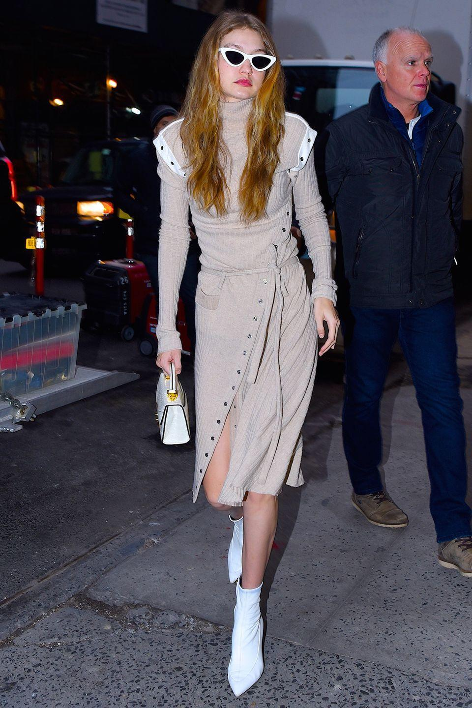 """<p>In an asymmetrical thigh-slit nude sweater dress, white ankle boots, and <a href=""""https://www.openingceremony.com/eyewear/adam-selman-x-le-specs/the-last-lolita-sunglasses_1477595828071.html?gclid=CjwKCAiA5OrTBRBlEiwAXXhT6C4KBN_rUpqry69qSViiGq2OLPQPxz4f_3VQeS0oqYewCqpTr1PUUBoC2LIQAvD_BwE&gclsrc=aw.ds"""" rel=""""nofollow noopener"""" target=""""_blank"""" data-ylk=""""slk:Adam Selman x Le Specs sunglasses"""" class=""""link rapid-noclick-resp"""">Adam Selman x Le Specs sunglasses</a> while out in Manhattan.</p>"""