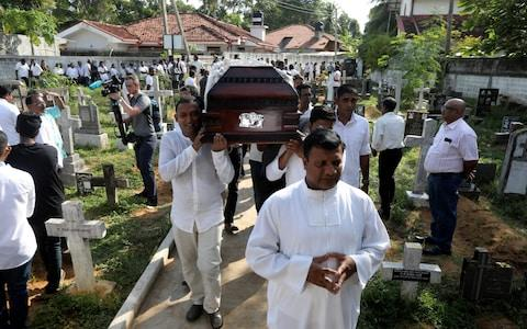 A coffin of a victim is carried during a mass burial of victims at a cemetery near St. Sebastian Church in Negombo. - Credit: ATHIT PERAWONGMETHA/ REUTERS