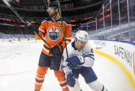 Edmonton Oilers' Adam Larsson (6) and Toronto Maple Leafs' Alex Barabanov (94) battle for the puck during first-period NHL hockey game action in Edmonton, Alberta, Monday, March 1, 2021. (Jason Franson/The Canadian Press via AP)