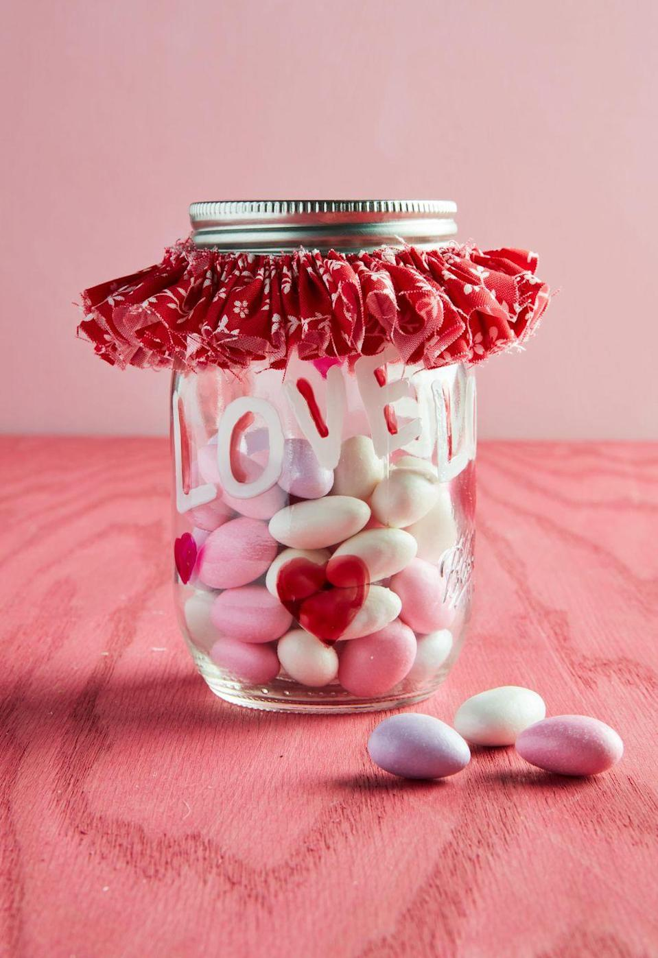 """<p>Transform a plain mason jar into a spectacular candy jar that is guaranteed to spark joy. </p><p><strong>To make:</strong> Write loving words and draw decorations on a mason jar with acrylic markers. To make the collar: Cut a long, 1-inch-wide strip of seasonally appropriate fabric. Using a needle and thread, sew a long, loose running stitch along one edge of the fabric, leaving lengths of thread at either end. Pull thread and fabric to create a ruffle. Use extra thread to tie the ruffle around the top of the jar. </p><p><a class=""""link rapid-noclick-resp"""" href=""""https://www.amazon.com/Acrylic-Painting-Ceramic-Porcelain-Permanent/dp/B07TTW3KLV/ref=sr_1_7?tag=syn-yahoo-20&ascsubtag=%5Bartid%7C10050.g.93%5Bsrc%7Cyahoo-us"""" rel=""""nofollow noopener"""" target=""""_blank"""" data-ylk=""""slk:SHOP PENS"""">SHOP PENS</a></p>"""