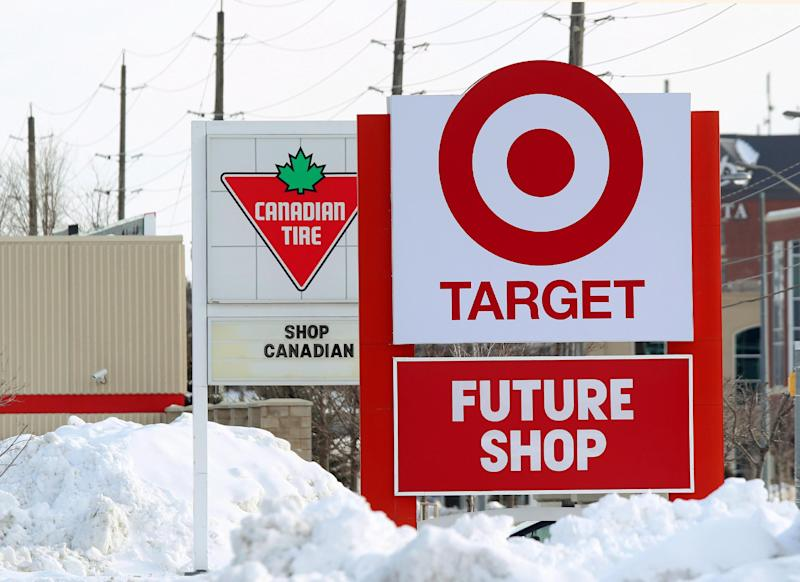 In this March 4, 2013 file photo, snow is piled in the parking lot of the new Target store in Guelph, Ontario as Canadian Tire posts a Canadian message on their sign. For years, Canadians would cross the border to the U.S. to shop at Target. Exporting its cheap chic there seemed like a no-brainer. But a year after opening more than 100 stores north of the border, Target has found business isn't so easy. Canadian Tire, which operates nearly 500 stores in the country and stocks housewares, barbecue grills and other items besides tires, has increased its marketing and deepened its assortment of home decor and other areas. (AP Photo/The Canadian Press, Dave Chidley)