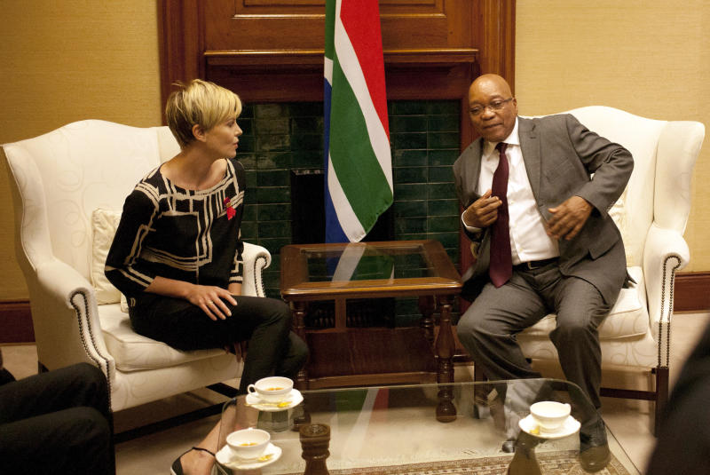"""South African President Jacob Zuma, right, meets South African-born Hollywood actress Charlize Theron, left, at his Union Building office in Pretoria, South Africa, Monday, 29 July 2013, ahead of their meeting, to discuss the fight against HIV and Aids, and """"how collaboration can assist mitigate the pandemic's negative impact on young girls"""". (AP Photo/Themba Hadebe)"""