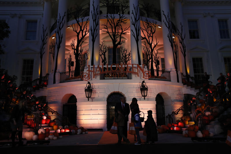 President Donald Trump and first lady Melania Trump give candy to children during a Halloween trick-or-treat event on the South Lawn of the White House which is decorated for Halloween, Monday, Oct. 28, 2019, in Washington. (AP Photo/Alex Brandon)