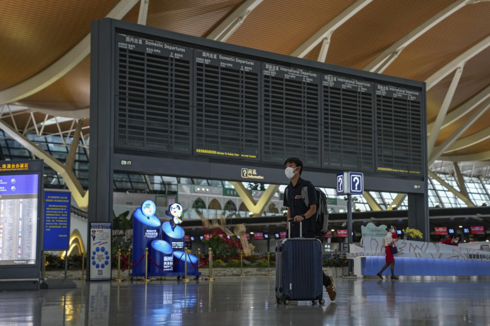 A passenger pushes his luggage past a blank flights information board at Pudong International Airport in Shanghai, China, Sunday, July 25, 2021. Airline flights were canceled in eastern China and cargo ships were ordered out of the area Saturday as Typhoon In-fa churned toward the mainland after dumping rain on Taiwan. (AP Photo/Andy Wong)