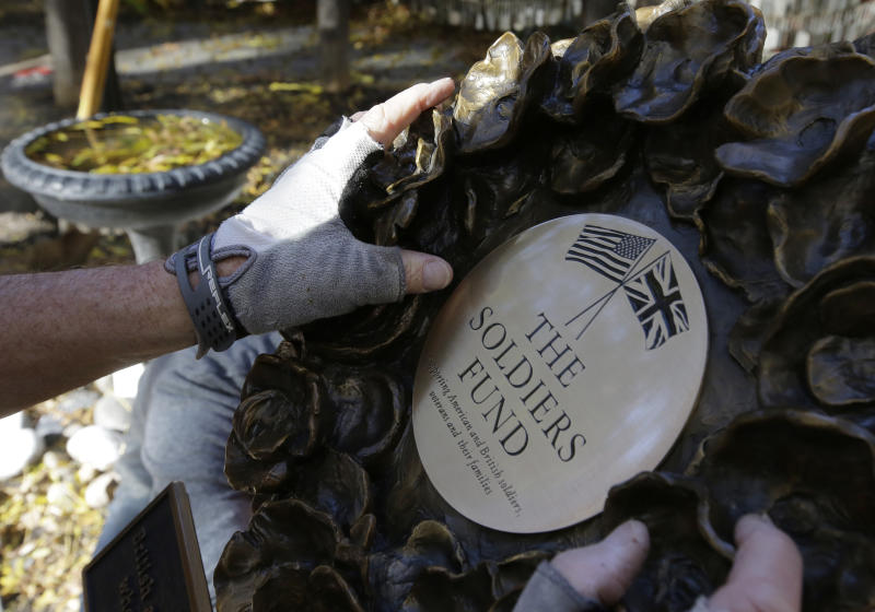 In this Wednesday, Nov. 7, 2018 photo James Re, of Boston, hands only, positions a bronze wreath as it becomes part of a memorial on the grounds of Old North Church, in Boston, that honors fallen soldiers from the U.S. and Britain. The memorial is being dedicated this month at an ironic venue - the Boston church where America's war for independence from England basically began. On Nov. 17, British and American military brass will unveil the bronze wreath and plaque at the church, saluting troops from both countries who have died in Iraq and Afghanistan. (AP Photo/Steven Senne)