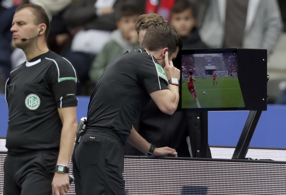 FILE - In this Sunday, Oct. 1, 2017 file photo, referee Harm Osmers looks at a video screen to decide whether to give a penalty against Bayern Munich during the German Bundesliga soccer match between Hertha BSC Berlin and FC Bayern Munich in Berlin, Germany. Footballs rules-making panel is advising FIFA to approve video review technology for referees before the World Cup. The panel, known as IFAB, says its technical experts made the recommendation Monday, Jan. 22, 2018 ahead of a March 2 meeting at FIFA which can decide. (AP Photo/Michael Sohn, file)