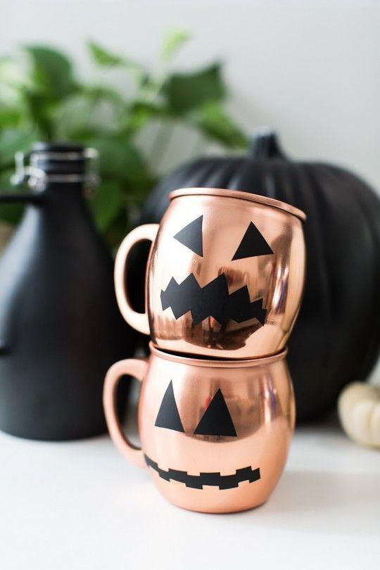"""<p>Cut a jack-o'-lantern face out of black window clings to transform your copper mule cups into mini pumpkins. Then cheers to your crafting skills by whipping up a seasonal cocktail. </p><p><a class=""""link rapid-noclick-resp"""" href=""""https://www.amazon.com/Moscow-Mule-Copper-Mugs-HANDCRAFTED/dp/B01LW4B7GK?tag=syn-yahoo-20&ascsubtag=%5Bartid%7C10055.g.421%5Bsrc%7Cyahoo-us"""" rel=""""nofollow noopener"""" target=""""_blank"""" data-ylk=""""slk:SHOP MOSCOW MULE MUGS"""">SHOP MOSCOW MULE MUGS</a></p><p><em><a href=""""https://sugarandcloth.com/diy-halloween-glassware-decals/"""" rel=""""nofollow noopener"""" target=""""_blank"""" data-ylk=""""slk:Get the tutorial at Sugar + Cloth »"""" class=""""link rapid-noclick-resp"""">Get the tutorial at Sugar + Cloth »</a></em> </p>"""