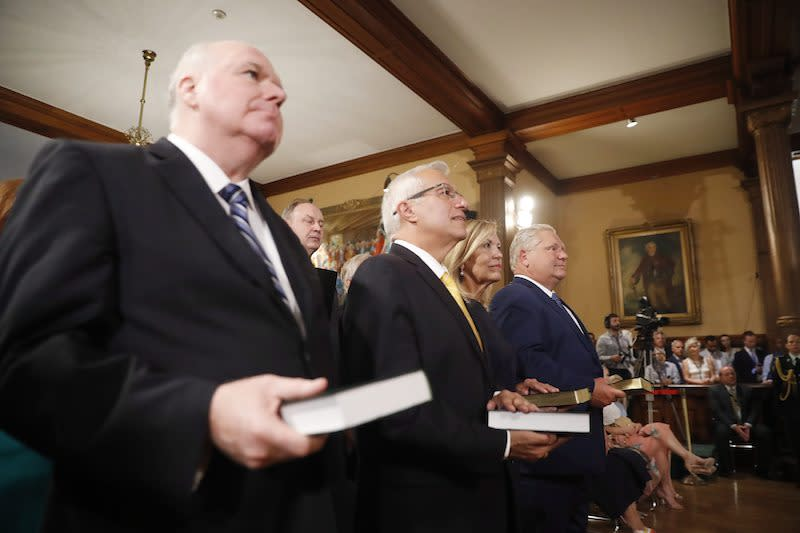 <p>From left, Jim Wilson, Vic Fedeli, Christine Elliott and Doug Ford stand for the swearing in ceremony of the new Progressive Conservative cabinet. Photo from The Canadian Press. </p>