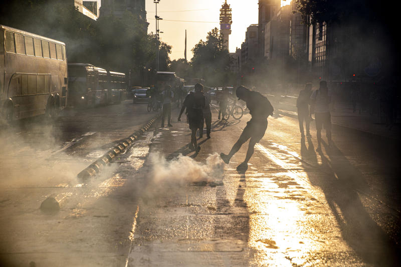 A protester kicks a tear gas canister launched by police near to the Santa Lucia subway station during a protest against the rising cost of subway and bus fares, in Santiago, Friday, Oct. 18, 2019. (AP Photo/Esteban Felix)