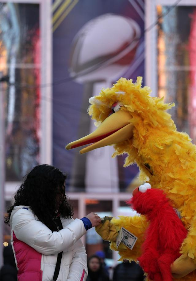 A street performer accepts a tip from a women in Times Square during Super Bowl Boulevard activities Wednesday, Jan. 29, 2014, in New York. The Seattle Seahawks are scheduled to play the Denver Broncos in the NFL Super Bowl XLVIII football game on Sunday, Feb. 2, in East Rutherford, N.J. (AP Photo/Charlie Riedel)