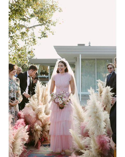 "<p>Mandy Moore <a href=""https://www.cosmopolitan.com/uk/fashion/celebrity/a25233730/mandy-moore-wedding-dress-pink/"" rel=""nofollow noopener"" target=""_blank"" data-ylk=""slk:wore a pale pink tulle Rodarte gown"" class=""link rapid-noclick-resp"">wore a pale pink tulle Rodarte gown</a>, which she had especially customised, for her wedding to musician Taylor Goldsmith in a private backyard ceremony. She paired with a matching pink veil for the most demure 'pretty in pink' look we've laid our eyes on. </p><p><a href=""https://www.instagram.com/p/Bqa1NjBg5Eg/?hl=en"" rel=""nofollow noopener"" target=""_blank"" data-ylk=""slk:See the original post on Instagram"" class=""link rapid-noclick-resp"">See the original post on Instagram</a></p>"