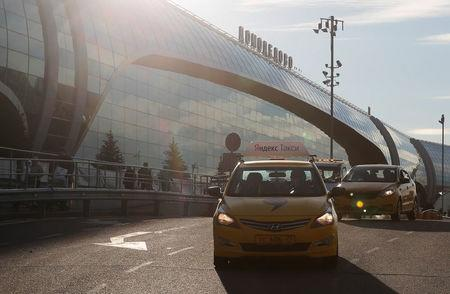 FILE PHOTO: A taxi with the logo of Russian online taxi service Yandex Taxi drives past a terminal of the Domodedovo Airport outside Moscow
