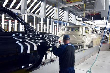 FILE PHOTO:  A Ford worker inspects paint work on the body of a Ford Expedition SUV at Ford's Kentucky Truck Plant in Louisville