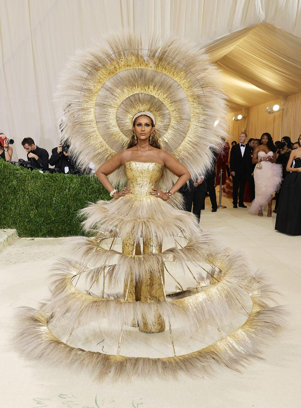 """<p>It takes a lot to steal attention on the Met Gala red carpet, but Iman managed to do exactly this in a striking look by Harris Reed. The model wore a completely handmade crinoline and gold leaf gown, jacquard bustier and flares, with an enormous statement hat which Reed created in collaboration with Vivienne Lake. The stylist described the moment as their """"biggest dream come true to date"""".</p>"""